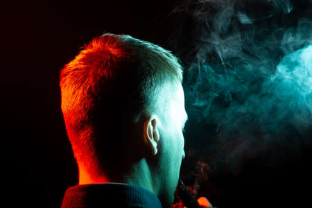 A view from the back on the head of a man in a shirt smoking a vape and exhaling multi-colored smoke of green and red at different directions from himself on a black isolated background Stock Photo