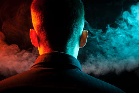 A view from the back on the head of a man in a shirt smoking a vape and exhaling multi-colored smoke of green and red at different directions from himself on a black isolated background Foto de archivo