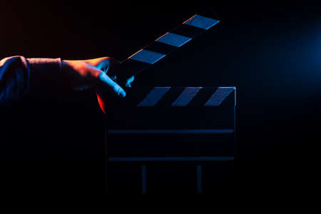 Opened clapperboard for cinema in hand, before filming on a black isolated background with red and blue backlighting Reklamní fotografie