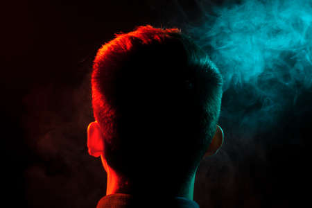 The view from the back of the smoker's head is highlighted in red and out of the green smoke raising his face up. Harm to human health. Stock Photo
