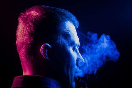 Una vista dalla parte posteriore della testa di un ragazzo intorno a una camicia che fuma una sigaretta ed espira fumo multicolore di blu sul lato destro da se stesso su uno sfondo nero isolato. Danno alla salute.