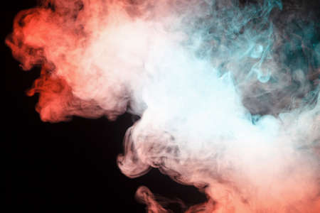 Multicolored smoke from a vape of green and red color of the strange mystical form on on a black isolated background. Bright clouds in the abstract form.