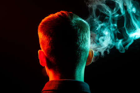 A view from the back on the head of a boy in a shirt smoking a vape and exhaling colored  green smoke at right direction from himself and with backlit red left on a black isolated background Archivio Fotografico