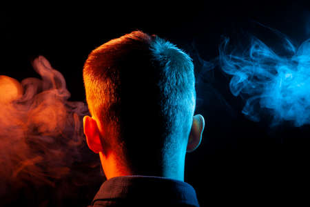 A view from the back on the head of a boy in a shirt smoking a vape and exhaling multi-colored smoke of blue and red at different directions from himself on a black isolated background
