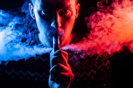 Portrait of a man with a shadow on a serious face  with a colored backlight of blue and red smoking a vape and exhaling multi-colored smoke in different directions on a black isolated background Stock Photo
