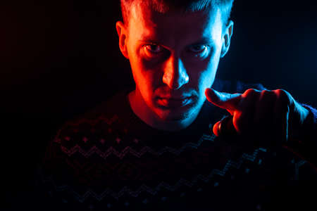Portrait of a short-haired guy with a shadow on a serious face dressed in a sweater with a colored backlight of blue and red points his finger at the viewer as Uncle Sam on a black isolated background. Imagens