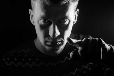 Portrait of a short-haired boy with a shadow on a serious face dressed in a sweater with a monochrome backlight points his finger at the viewer as Uncle Sam on a black isolated background. Stock Photo