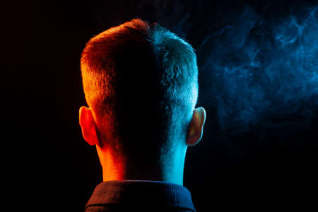 A view from the back on the head of a boy in a shirt smoking a vape and exhaling multi-colored smoke of green and red at different directions from himself