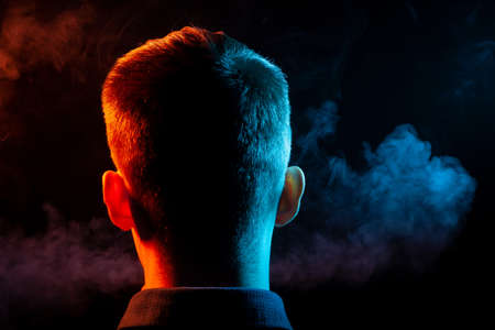 A view from the back on the head of a guy in a shirt smoking a vape and exhaling multi-colored smoke of green and red at different directions from himself