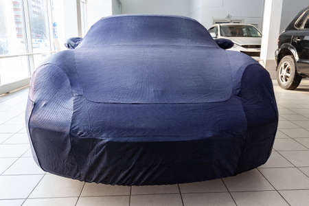 A car in the garage, carefully prepared for winter storage, covered with a professional cover made of blue special material, made to order, perfectly sized.