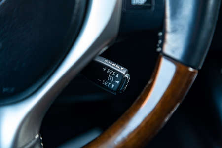 The shift lever to set the automatic cruise control speed inside the car close-up located near the steering wheel in black with white signs and symbols of beautiful design in the interior.
