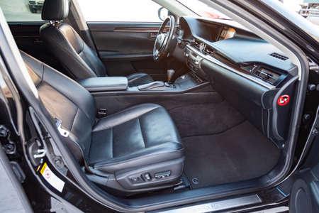 Interieur im Auto: Beifahrersitz, überzogen mit echtem schwarzem Leder, modernes Interieurdesign mit Holzelementen, luxuriöses zentrales Bedienfeld.