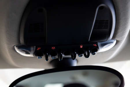 Lighting control inside the car from the top on the instrument panel behind the rear-view mirror in black with buttons and red illumination close-up.