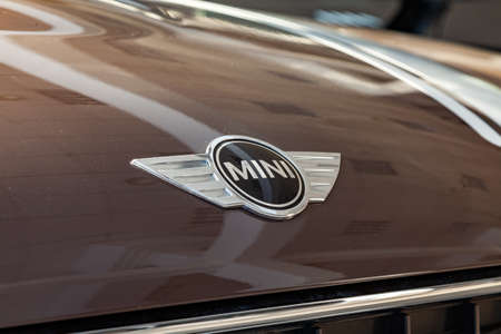 Novosibirsk, Russia - 08.01.2018: A stylish chrome-plated shiny brand logo on a polished light-reflecting bonnet of an expensive vehicle with a mini Cooper model close-up. Manufacturer Sign.