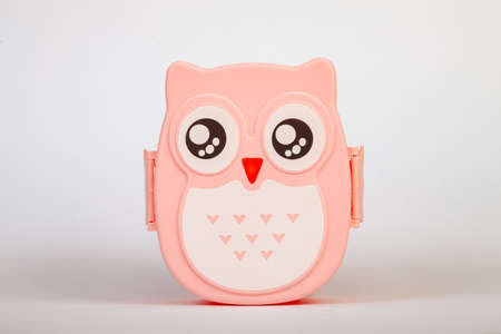 Lunchbox in the form of a pink owl for preserving and carrying homemade food or sandwiches during working day on white isolated background. Banque d'images