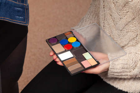 A palette of shadows with different colors of the product in the hands of a model in a beauty studio, with which makeup is applied using it.
