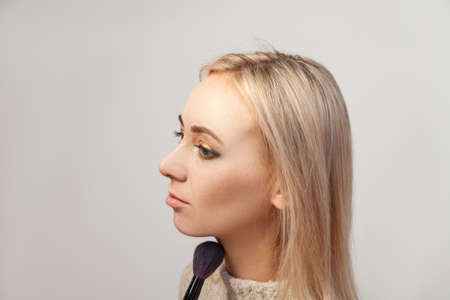 Profile of a blonde model with blue eyes on a white background which impose make-up in the studio, the makeup artist with a brush in her hand contours the face with tone, powder and blush. Фото со стока