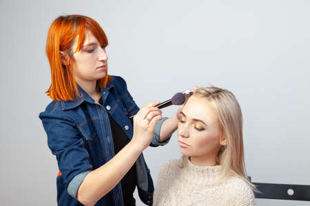 Blonde girl's with closed eyes and oriental style makeup on the eyelids in a beauty studio on a white background, the visagiste draws the outline of the face puting tone with a brush in his hand.