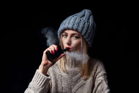 The girl the blonde in a knitted sweater and hat holds in her hand with a manicure an electronic cigarette vape and inhales smoke with her lips painted with red lipstick.
