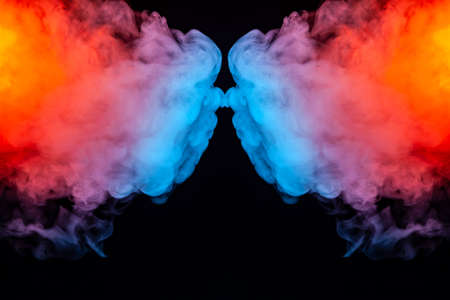 Soaring thick colorful smoke iridescent like a rainbow in bright colors divided into two halves on a black background swirling in waves.