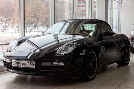 Novosibirsk, Russia - 08.01.2018: Front view of the 2006 sport porsche boxster s sedan prepared for sale and exhibited in the showroom with a polished shiny black body and a license plate of a region in Russia. Redactioneel