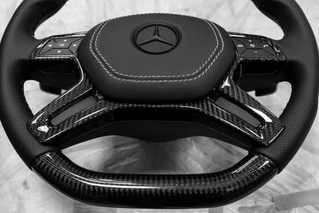 Novosibirsk, Russia - 08.01.2018: Carbon steering wheel of a black car in the workshop tightened and perforated with natural leather close up with the brand sign of Mercedes covered with matte paint