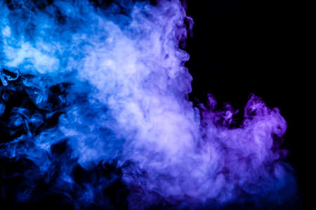 Clubs of colored smoke of blue and pink color on a black isolated background in the form of soft clouds from the vape Stock fotó