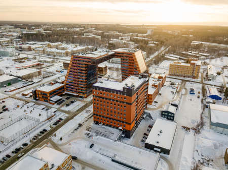 Aerial view of academpark technopark of the Novosibirsk Academic Township - large building with laboratories and innovative projects, technical inventions covered with snow on a winter day at sunset Foto de archivo