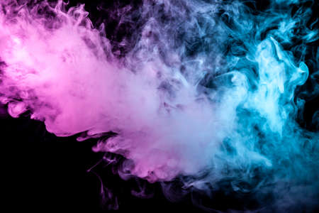 Multicolor, thick smoke, illuminated by colored in blue, purple and pink light against a dark black isolated background, welded with clubs and curls, rising from a steam of vape. Wind blow Banco de Imagens