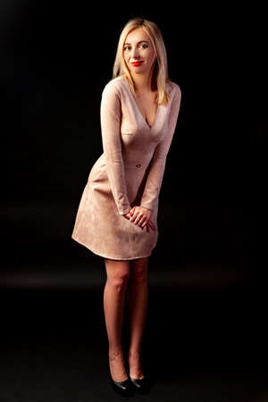 Young blonde girl with bright make-up and red lips is standing in the studio on a dark background in a beige dress and black shoes with her hands together in front of her and slightly leaning forward.