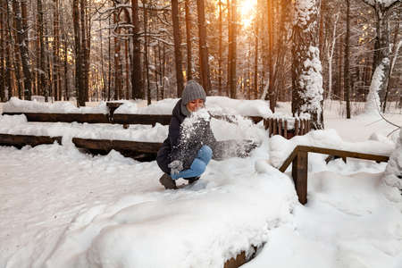 A blonde girl in a gray hat and gloves and a winter jacket squatted in front of a snowdrift and playing with the snow tossing it up and smiling in the forest against the background of a wooden bench. Stockfoto