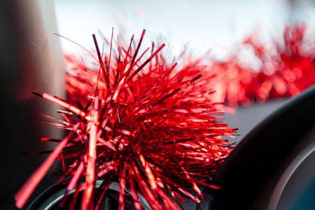 Brilliant red tinsel inside the car decorates the dashboard above the steering wheel flickering and uplifting the drivers excitement distracts from the gray everyday and brings the Christmas closer.