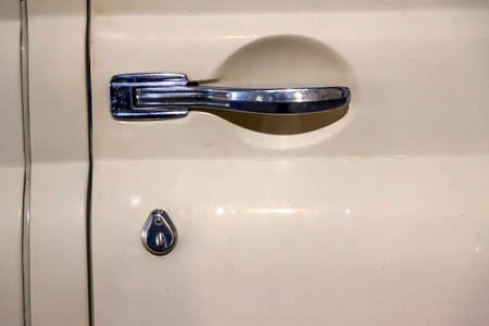 Novosibirsk, Russia - 01.30.19: View on closed front door with handle and keyhole of the old Russian car of the executive class released in the Soviet Union beige GAZ m-20 pobeda