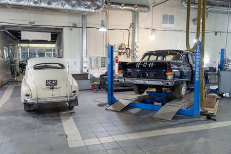 Novosibirsk, Russia - 01.30.19: Rear view on two Russian classic vintage cars gaz m20 pobeda and 13 chaika in a repair shop in good condition one of then standing on lift Editöryel