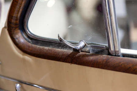 Novosibirsk, Russia - 01.30.19: View on opened front door with handle for opening the corner window of the old Russian car of the executive class released in the Soviet Union beige GAZ m-20 pobeda