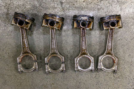 Four silvery metal car pistons in poor condition removed from the used engine in a deposit of oil lying on concrete in a vehicle repair shop for washing and restoration Imagens