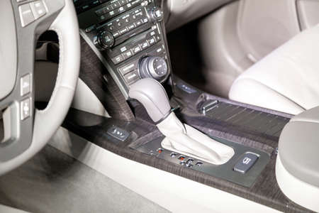 The interior of the car with a view of the steering wheel, dashboard, seats and gear shift with light gray leather