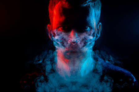 Portrait of a man who is angry and has bad emotions with mask from a smoke around on a black isolated background. The face of the guy in the shade with color red and blue illumination.