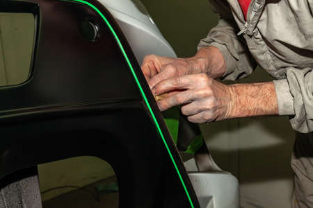 A car repair worker during work pastes with an  green adhesive tape a part of the body element of white color in order not to fill it with paint during painting in a workshop on repair of vehicles