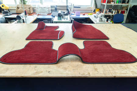 Car 3D handmade floor mats of red color from wool for front and rear passengers of a vehicle in an interior design workshop with tools