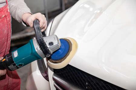 Der Meister der Detaillierung in Arbeitskleidung und schmutzigen Händen poliert die Karosserie der Motorhaube des Autos mit einer Poliermaschine in der Werkstatt für Karosseriereparaturwagen in Weiß