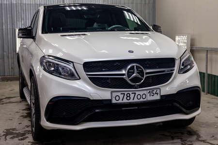 Novosibirsk, Russia - 08.01.18: Front view of luxury very expensive new white Mercedes-Benz GLE Coupe AMG 63s car stands in the washing box waiting for repair in auto service