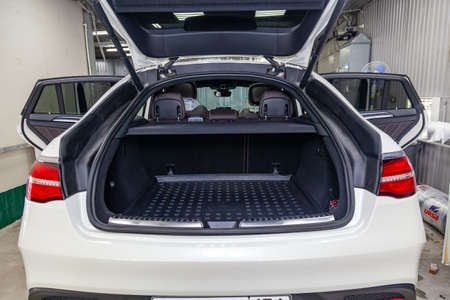 Novosibirsk, Russia - 08.01.18: Rear view of luxury very expensive new white Mercedes-Benz GLE Coupe AMG 63s car stands with opened trunk in the washing box waiting for repair in auto service