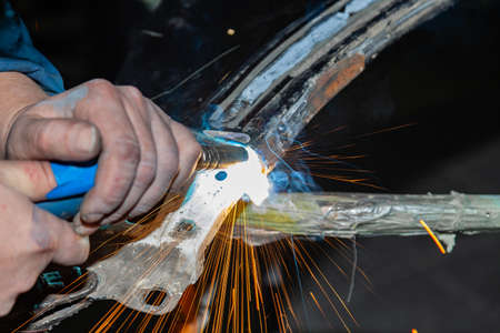 Close-up view strong man is a welder in blue working overalls without gloves on arms, a metal product is welded with a welding machine in the garage workshop, blue and orange sparks fly to the sides