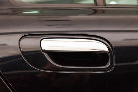 View on closed black front door with handle made from chromium of luxury car after detailing and polishing 版權商用圖片