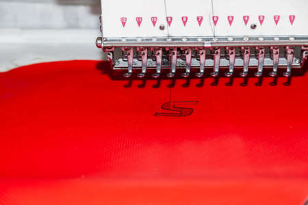 Industrial white sewing machine for embroidery makes black logo with letter S  with black thread on a red background from perforated leather Фото со стока