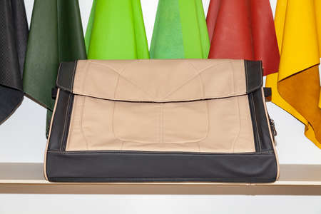 Handmade brown and beige leather organizer bag for a car trunk for storing things and tools in a shop in a vehicle interior design workshop against the background of skin samples of different colors Stock Photo