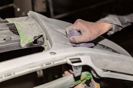 A boy prepares a car body element for painting after an accident with the help of abrasive paper in a car repair shop. Recovery bumper after a collision. Stock fotó