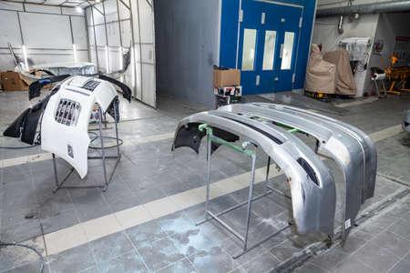 Tres partes de parachoques de automóviles se instalan en los bastidores después de pintar en el taller de reparación de automóviles en la habitación con herramientas y equipos para reparar partes del cuerpo después de un accidente. Foto de archivo