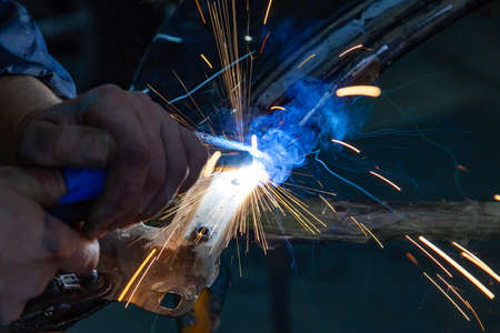 Close-up view strong man is a welder in working overalls without gloves on arms, a metal product is welded with a welding machine in the garage workshop, blue smoke and orange sparks fly to the sides Imagens